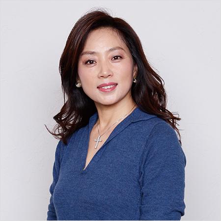 紺のシャツを着て微笑んでいるネックレスを付けた藤吉久美子の画像