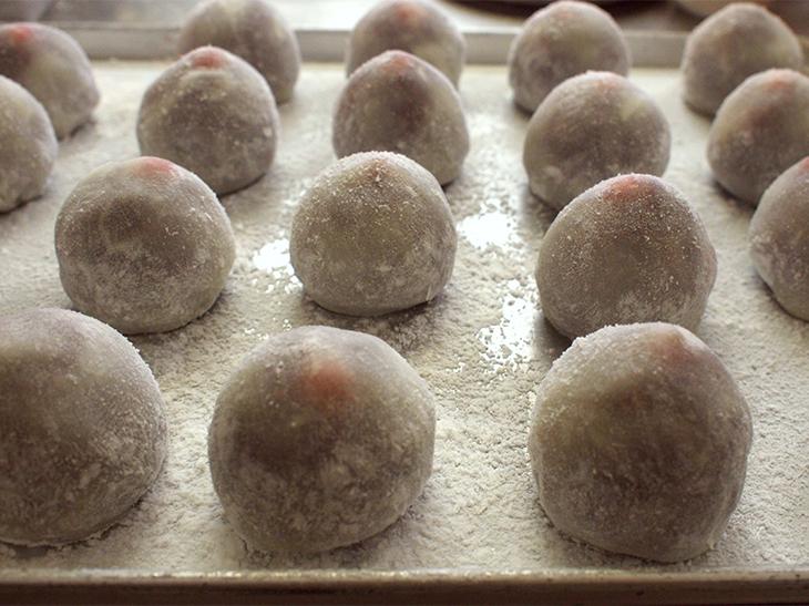 作業場で出番を待つ、粉化粧した苺大福たち。立派な苺の頭が求肥から今にも飛び出しそう。
