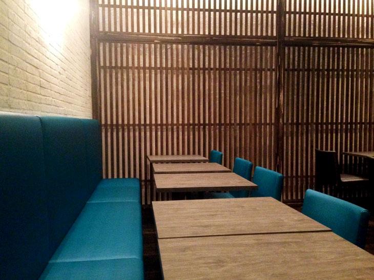 格子の壁と白いレンガの和洋折衷インテリア。テーブル席のほか、4名用の畳の小上がりもある