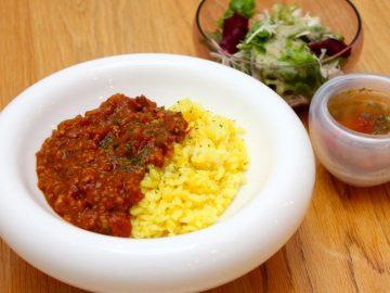 白いガラスの深皿「スポーラ」に、キーマカレー1,080円(サラダ又はピクルス、小スープ付き)の鮮やかな色が映える。元は花器として製品化されたものだが、軽やかな存在感がフレンチのシェフたちの目に止まり、食器としても活用されている(スープの器は「エアーリップ」、サラダは「ベレッツァ」。ともに人気商品)。