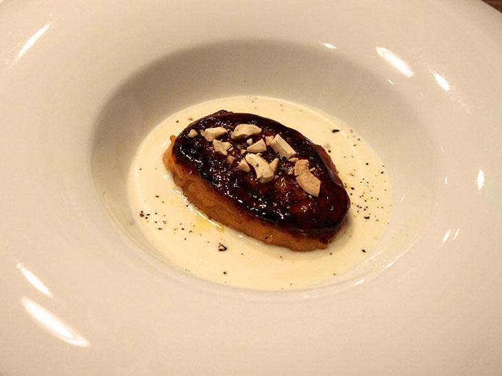 """二つ目の前菜(温製)の「カボチャの焼きニョッキ、グラナ・パダーノのチーズクリームソース」。チーズソースの塩気と、かぼちゃの甘みが生み出す""""甘じょっぱさ""""が魅力の一皿。"""