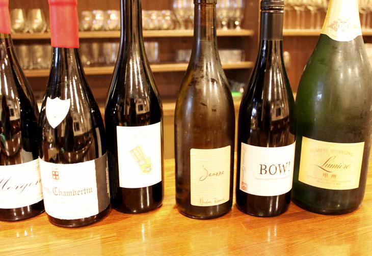 """亜美さんセレクトのワインは、国産・海外産問わず料理に合うものが中心。右から順に、山中シェフの修業先の一つである山梨の老舗ワイナリー「ルミエール」のスパークリング甲州(白)、同じく山梨の「ドメーヌ・オヤマダBOW!ルージュ」(赤)と続き、左端の「マルセル ラピエール モルゴン」(赤)まで、ワイン好きがうなる錚々たる品揃え。中でも、「マルセル ラピエール モルゴン」は、""""自然派ワインの父""""と呼ばれたマルセル・ラピエールが亡くなる前に手がけた最後の年のもので、貴重な一本だ。スパークリング(グラス)800円~、白ワイン・赤ワイン(グラス)700円~。"""