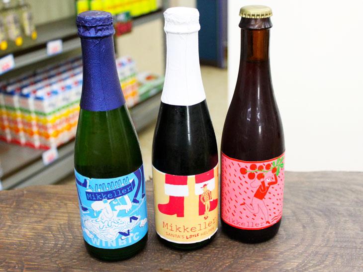 """特定の醸造所を持たない""""ファントムブルワリー""""の「ミッケラー」(デンマーク)が、ベルギーで醸造した愛らしいビールたち。中央の「ミッケラー サンタズ・リトルヘルパー コニャック樽 クリスマス限定」は、濃厚な高アルコールのエールビール「サンタズ・リトルヘルパー」をコニャック樽で熟成したクリスマス限定ビール。1本1,500円。"""
