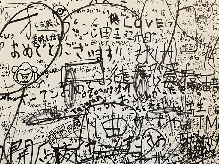 壁一面に書かれたファンのメッセージ。白壁が見えないほどの書き込み量が、店の人気ぶり、美味しさを表している