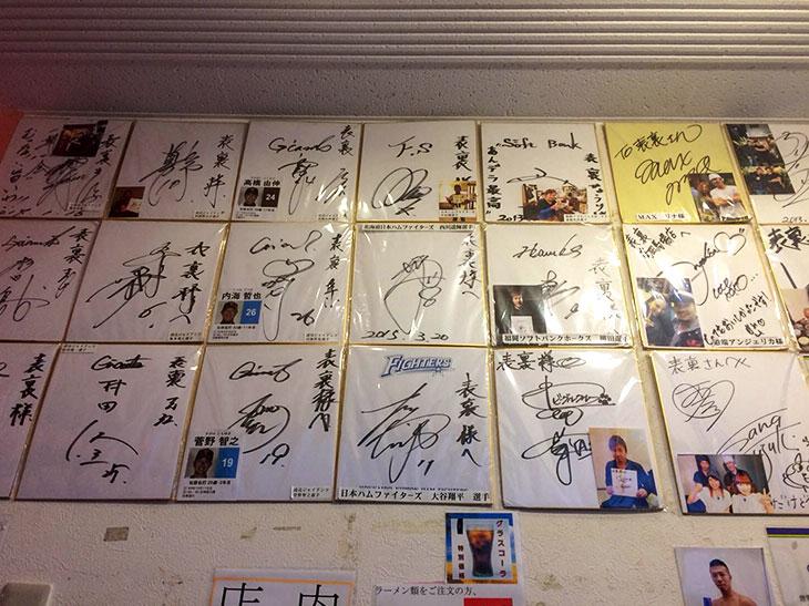 店内は細長く、長いカウンター席とテーブル席。壁にずらりと並ぶ色紙。プロ野球選手や格闘家など、有名人のサインが30枚以上貼ってある