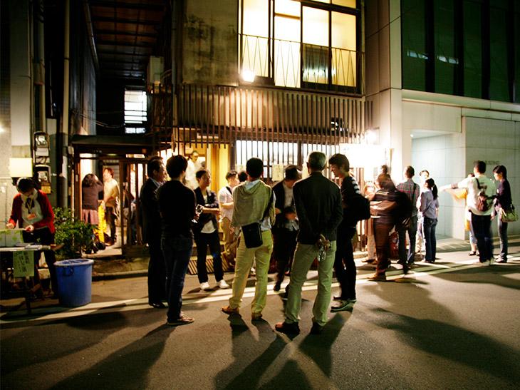 過去のイベント当日の風景。ワイングラスを片手に、次はどの店に行こうか楽しげに話す人たちが新富町の街にあふれる