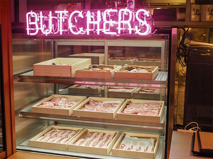 入口には店舗で使用する豚肉が、豚バラ、肩ロース、豚トロなどに分けられて、まるでアート作品のようにディスプレイされている