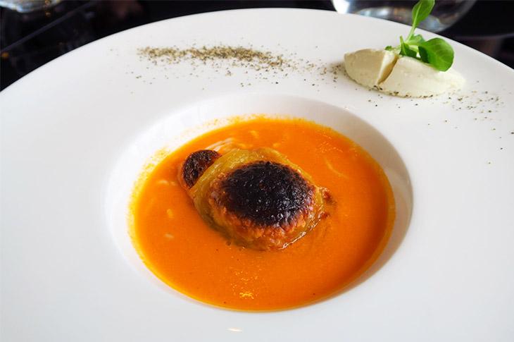 """「ローストトマトスープ""""BEYOND TOFUのグラチネ"""" """"ナチュラルとうふ""""と""""低糖質とうふ麺""""を添えて」は、BEYOND TOFUを加熱してきれいに焼き色を付けている。なめらかな舌触りが印象的な一皿だ"""