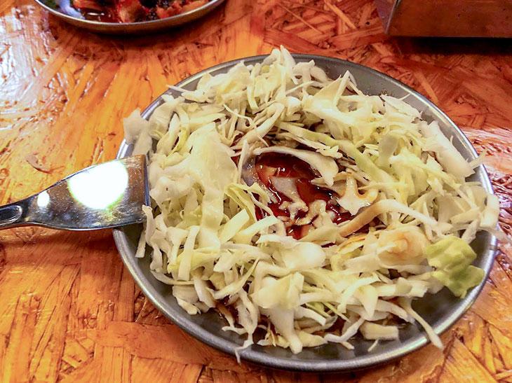 キャベツをヘラで刻み、タレとにんにくと唐辛子で食べる。さっぱりして肉との相性バッチリ