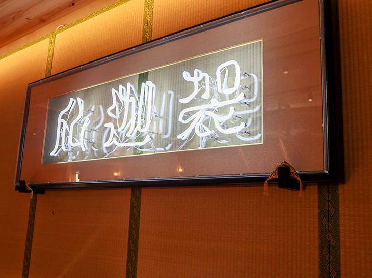 壁に掛けられた畳の上のネオンには「仏迦袈(ぶっかけ)」という文字が飾られています