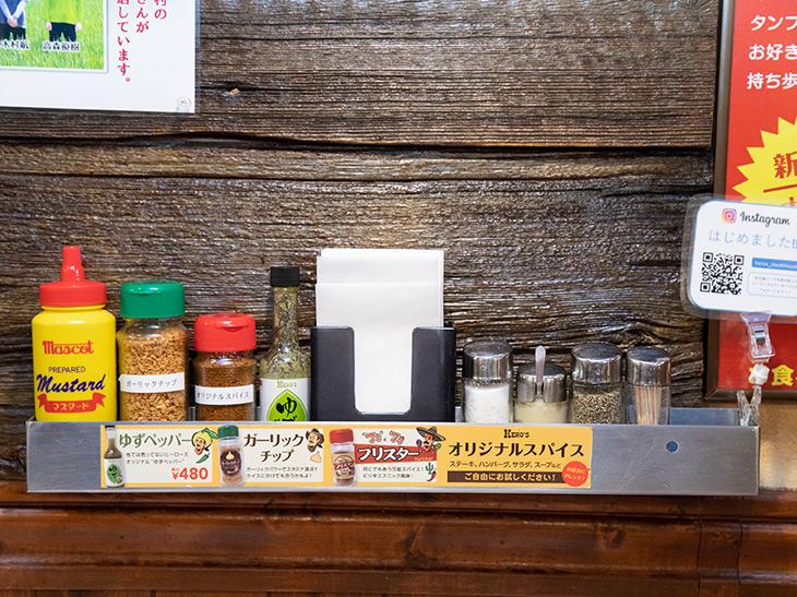左から、マスタード、ガーリックチップ、オリジナルスパイス、ゆずペッパーのボトル。生にんにくやコショウ・塩もあるので、さまざまな味を楽しめます