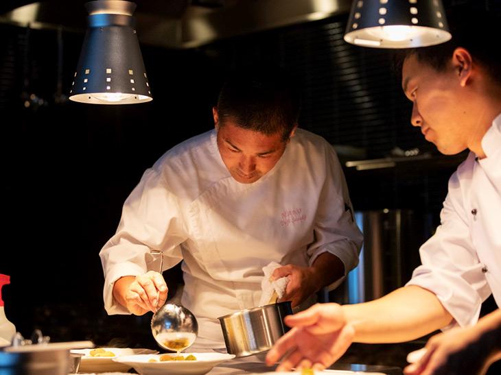 ドラマティックなライティングのレストラン内オープンキッチンで、熱のこもった動きを魅せる佐々木シェフ(中央)。料理をしている時の瞳の強さが実に印象的だった
