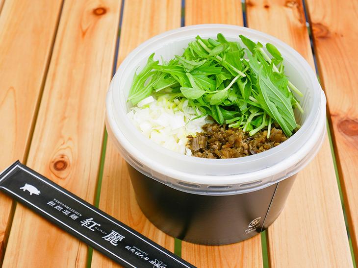容器は二段になっており、下の容器には麺が、上の容器には高菜、ネギ、水菜などが入っている