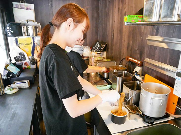 フードトラック内という限られたスペースで手際よく担担混麺を作っていくスタッフ