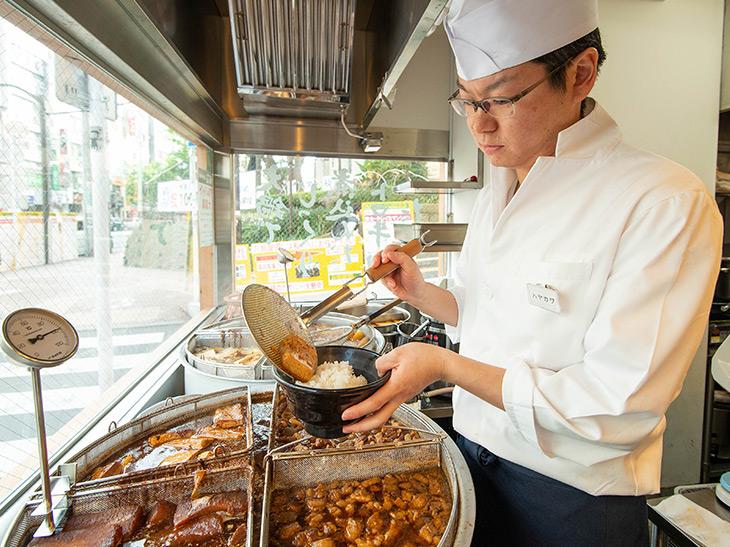 営業部の早川さん。注文後、大鍋から最適な状態の肉や卵などをゴハンの上に。