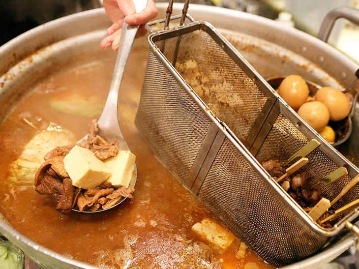 大鍋の中で煮込まれたモツや豆腐。串物が浸かったザルの向こうには煮卵も