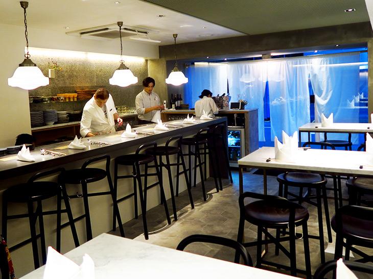 店の外観は大きな白い暖簾がかかったいかにも和食店という趣き。店内に入るとグレーの大きなカウンターや白を貴重にした大理石など、スタイリッシュな雰囲気が漂う