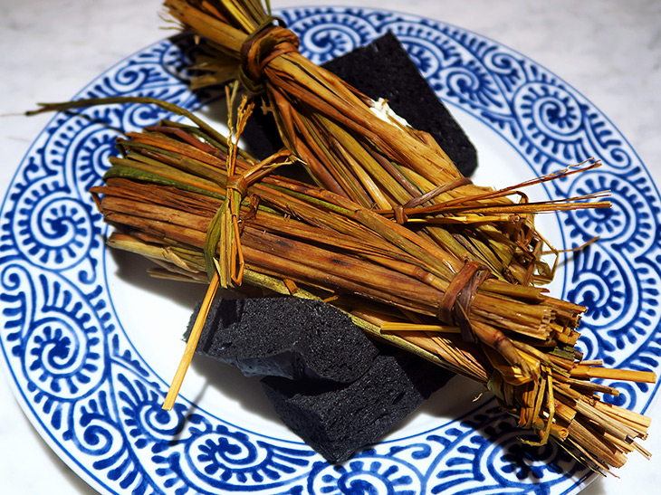 お椀と一緒に出てきたのは藁に包まれた添え物。黒いものは炭に見立てたパンだった
