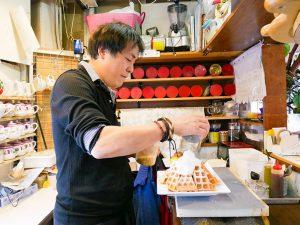 「でかもりスイーツマウンテン」の盛り付けをするオーナーの嶋田さん。駅反対側にあるコーヒー専門店『cafeAiR ROSTARY』のオーナーでもある