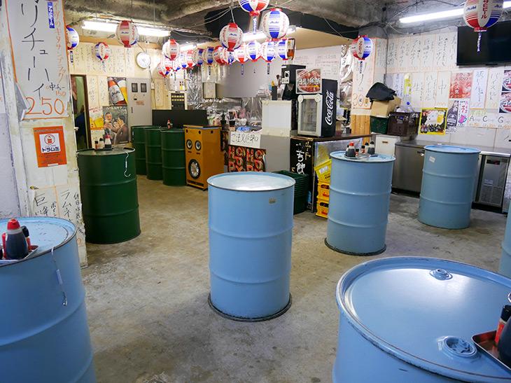 水色のドラム缶が、ほどよい距離感で並べられた店内。壁にはメニューの札がぎっしり