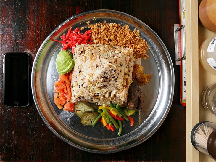 コシャリの周りのトッピング、上から逆時計回りに、フライドオニオンチップ、紅生姜、アボカド、カットトマト、温野菜、焼きパイナップル、コフタ(エジプト風牛のつくね)など。カラフル!
