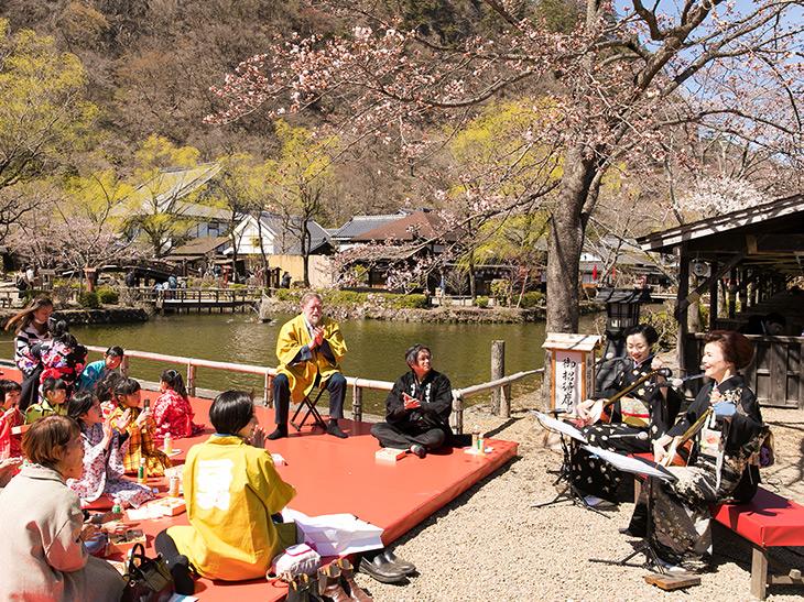 船着き場の桜の下、端唄に手拍子を打ちながら花見弁当を楽しむ子どもたち