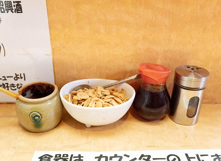 卓上には麻辣醤、ニンニクチップ、ラー油、山椒が。さらに辛く、痺れる味に味変可能
