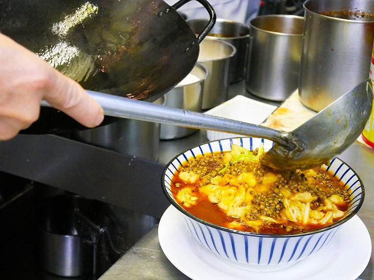 鉄鍋で熱くした山椒を最後にかけて完成。店1、2を争う人気料理