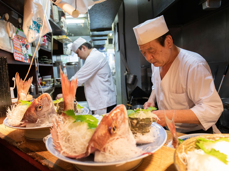"""""""新八のレジェンド""""こと千葉さん。この日の刺身の盛り合わせは鯛やサザエなど旬の魚介6種。目がキラキラと澄んだ鯛のお頭で鮮度の良さがわかる"""