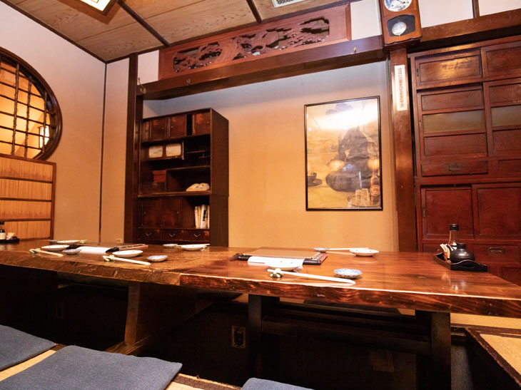 小上がりの座敷席。奥の茶箪笥は女将の祖母が使っていたもの。鴨居や掛け時計、格子の窓などがいい雰囲気
