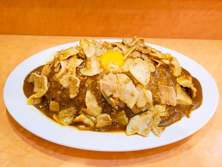 「スタミナカレー(生玉子入り)」820円+特盛620円、トータル1440円。ご飯を埋め尽くすルーの上には生姜焼肉そして卵の黄身が