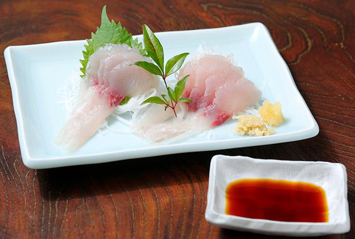 「鯉生刺」600円。ほんのりピンク色の透き通った身。生姜やニンニクをちょっと載せて