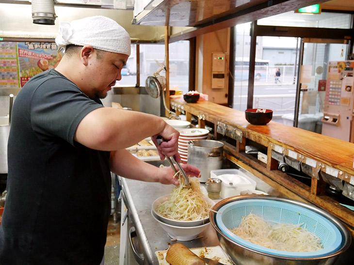 ヤサイの山をガシガシと作る店長の小寺さん。美味しさはもちろんですが、高い山を作る技術、すごいです