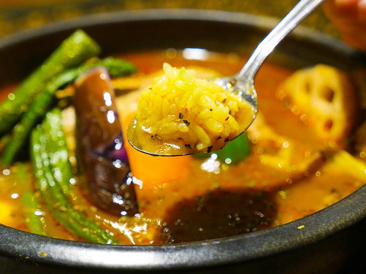 ライスをスプーンにのせ、スープに浸して一口! 香辛料の華やかな味わい