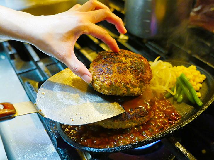 焼いたハンバーグを、熱々の鉄板に乗せて完成。ソースが沸き立つ!