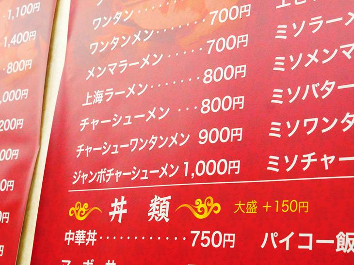 壁に貼られたメニュー「15年前は750円だったね~」(オーナーの陳さん)
