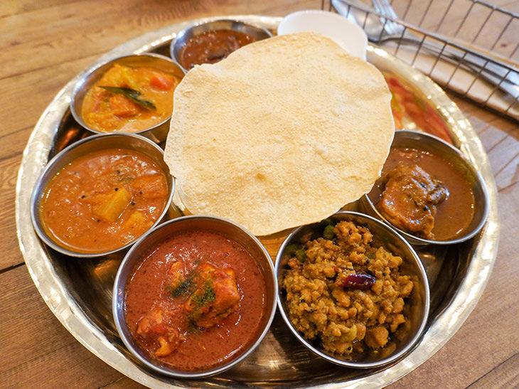 ランチの「全部のせプレート」1500円は、カレー6種類と無糖のヨーグルト、真ん中のパパド(豆のおせんべい)の下にはライス(おかわり自由)。この他にサラダ、インドのお茶が付く