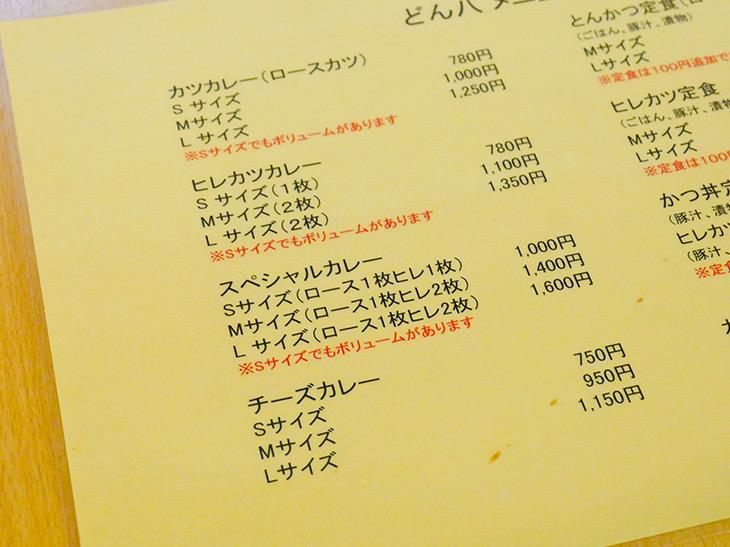 メニュー表。カツカレーとトンカツ定食を軸に、S、M、Lなどサイズごとの値段が。定食は100円追加でご飯大盛りに
