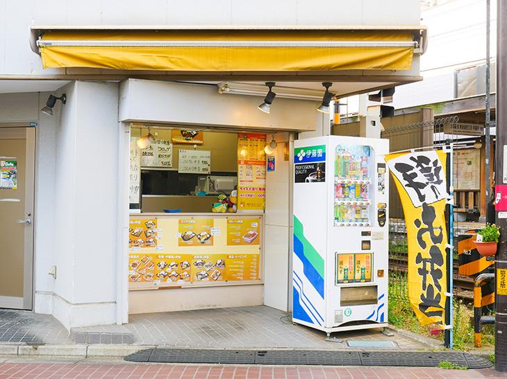 黄色ののぼりとひさしが目印。店のすぐ横は踏切
