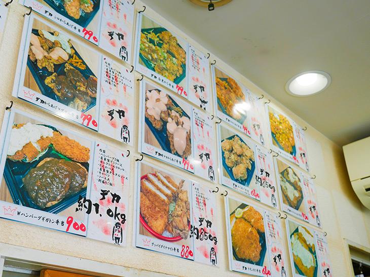 店の壁に貼られた写真付きのお弁当メニュー。でかい弁当には「デカ」の文字と手形が。どすこーい感溢れてます