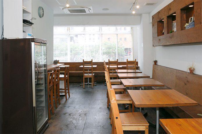 北欧スタイル、木の机と椅子でナチュラルな雰囲気の店内。窓からは明るい日差しが降り注ぐ