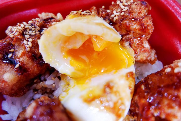 卵を箸で割ると、黄身がトロリと。肉につけて食べると美味!