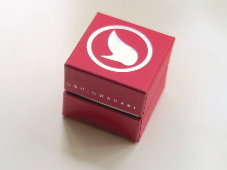 外箱は職人がほぼすべての工程を手作業で行う印籠式貼り箱。万城食品のコーポレートカラーで日本の伝統色でもある「深緋(こひき)」を使用
