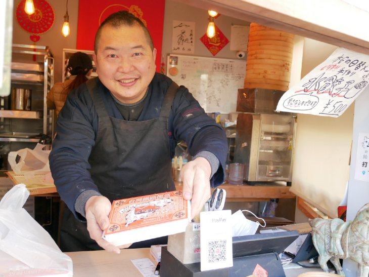 店主の邱 任遠(キュウ レンエン)さん。手にしているのは人気の「台湾鉄道弁当」