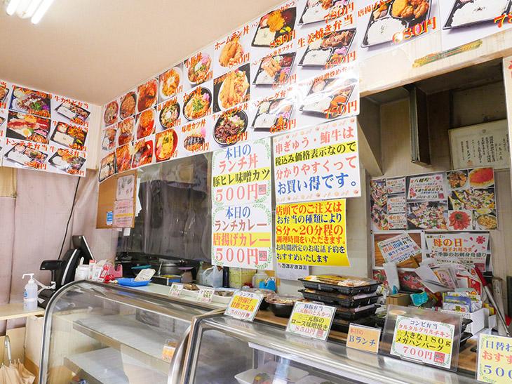 店の壁いっぱいに写真入り弁当メニュー。日替わりメニューは500円~とリーズナブル