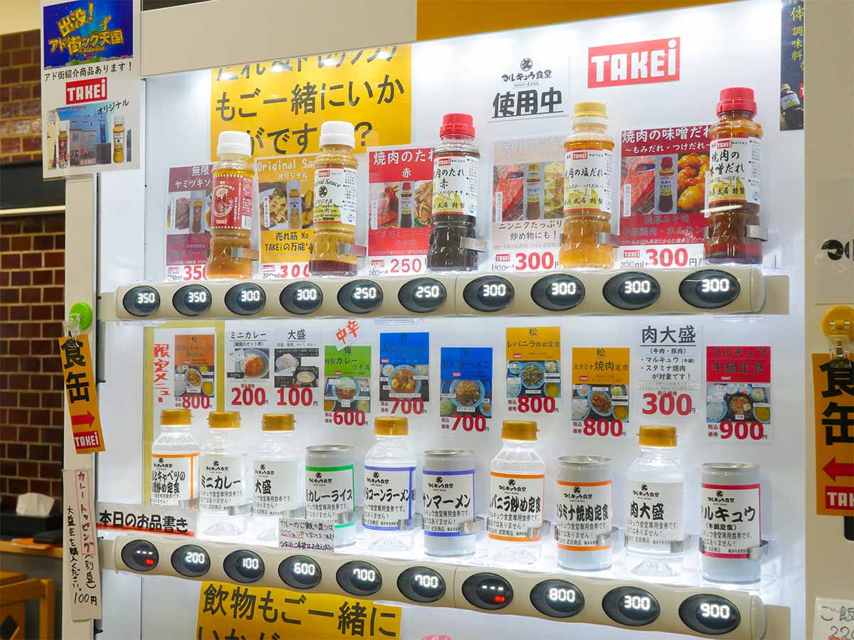 店に入ってすぐの場所にある自動販売機。食券じゃない、料理名が書かれたボトルをカウンターに
