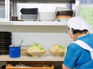 カウンターの奥でどんどん具材を盛り付けていくママさん。青い容器の中には自家製の肉味噌が