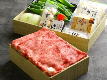 京都産黒毛和牛(肩ロース、カタ)すき焼き用450g、九条ねぎ100g、玉ねぎ1個、ささがきごぼう1袋(80g)、麩1袋、糸こんにゃく1袋(250g)、豆腐1パック、ざらめ1袋(100g)、割り下1本がセットになっている。約2~3名分