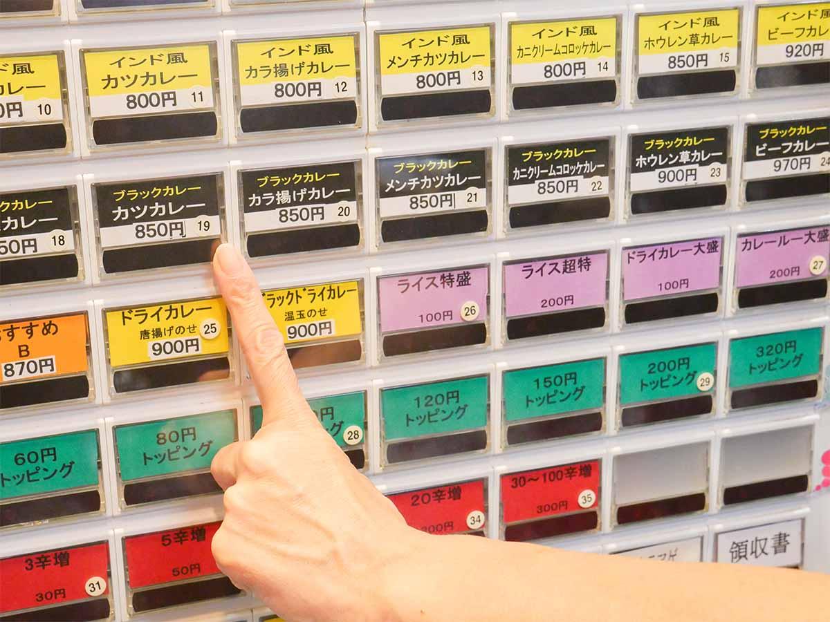 券売機。今回は店名物のブラックカレーのカツカレーにライスとルーを追加